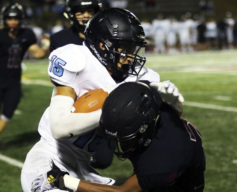 PMG PHOTO: DAN BROOD - Lakeridge junior Tyeson Thomas (15) takes a hit as he returns the second-half kickoff during the Pacers' game with Tualatin on Friday.