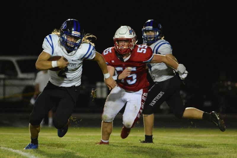 PMG PHOTO: DAVID BALL - Centennial rusher Connor Tolstad flushes South Medford QB Toren Tuttle out of the pocket on a play early in the third quarter.