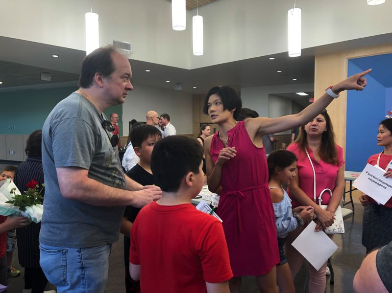 PMG PHOTO: STEPHANIE BASALYGA - Dianna Ngai, Beatrice Morrow Cannady Elementary principal, directs the family of a student to the appropriate classroom during an Aug. 29 ribbon-cutting event that gave students a chance to walk through the new building.