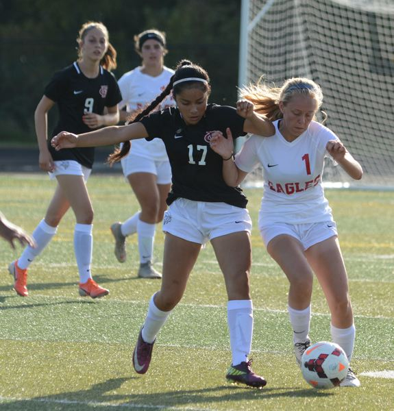 PMG PHOTO: DAVID BALL - Centennials Alexi Howard (1) fends off a Forest Grove player during a jamboree. She scored with eight seconds left in the Eagles 3-0 win over Roosevelt on Thursday.