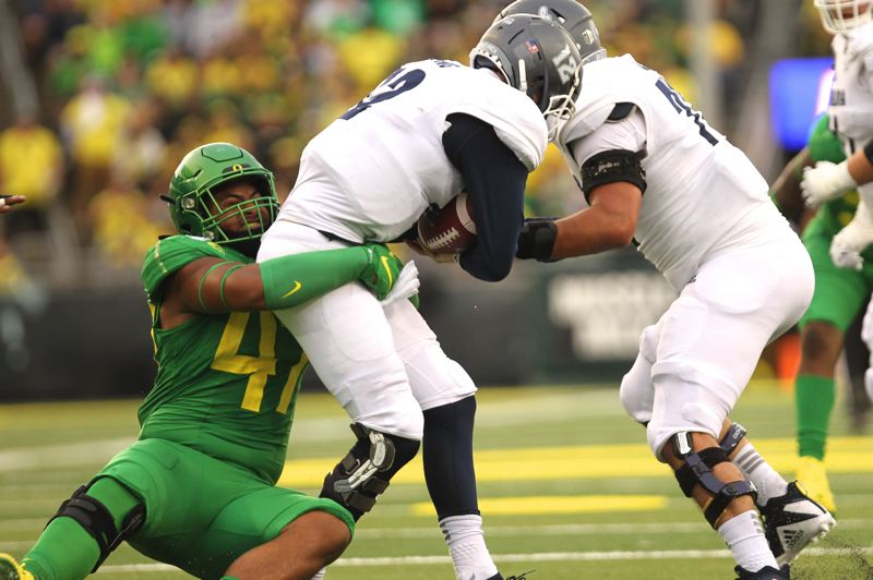 PMG PHOTO: JAIME VALDEZ - Oregon Ducks linebacker Mase Funa (left) sacks Nevada Wolf Pack quarterback Carson Strong.