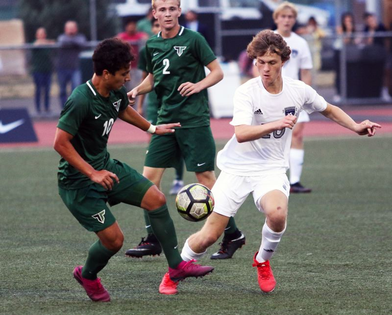PMG PHOTO: DAN BROOD - Tigard High School senior Marcos Milan (left) and Wilsonville's Elijah Powelson fight for the ball during the Tigers' 4-2 victory on Thursday.