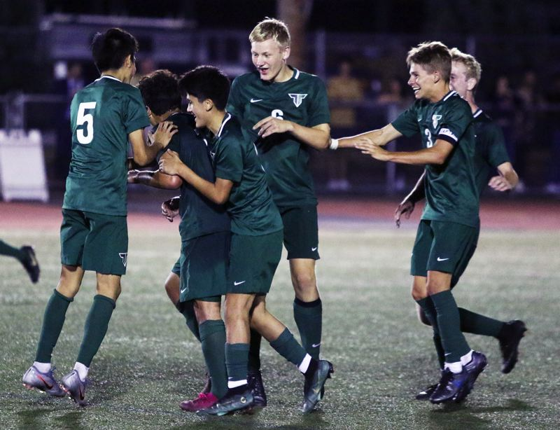 PMG PHOTO: DAN BROOD - Members of the Tigard High School boys soccer team celebrate following the Tigers' 4-2 come-from-behind victory over Wilsonville.