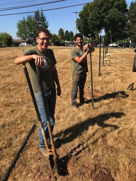 COURTESY PHOTO: ADAM KOHL - Creating community gardens is not a desk job. Adam Kohl with Gabriel Blustein putting in a fence at  Outgrowing Hunger's most recent garden on ground owned by Adventist Health.