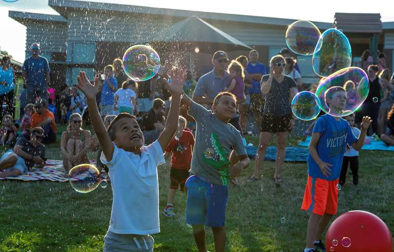 PMG PHOTO: CLARA HOWELL  - Lowrie Primary families enjoy the giant bubble show during the back-to-school gathering Sept. 6.