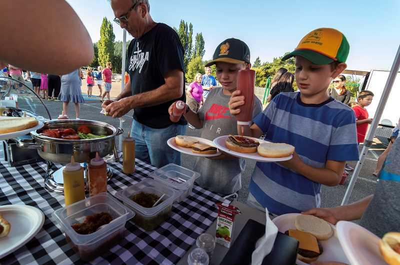 PMG PHOTO: CLARA HOWELL - Stafford Primary families line up for barbecue food during the Stafford Stampede.