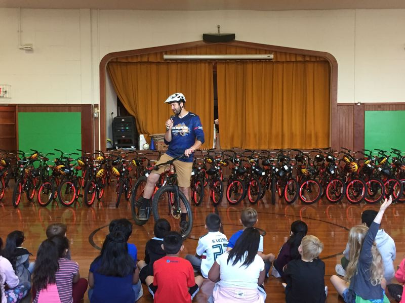COURTESY PHOTO: CAN'D AID FOUNDATION - Jeff Lenosky, a professional cyclist, talks to students at Reedville Elementary School on Friday, Sept. 6, in front of a row of bikes that were donated to the first- and second-grade classes at the school.