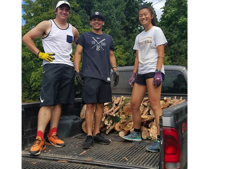Gladstone High School alumni Ben McCoy, Damian Alvarado and Renee Baker load firewood for donation to families in need.