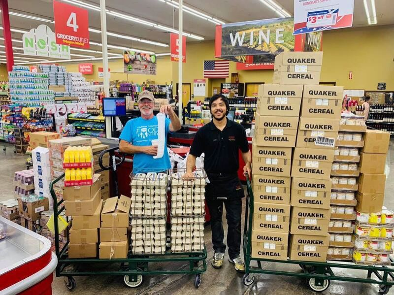 COURTESY PHOTO - On the left, volunteer Dan Oberg picks up a large food order for the Gladstone Food Pantry. Oak Grove's Grocery Outlet raised $15,633 in July for two local food pantries.