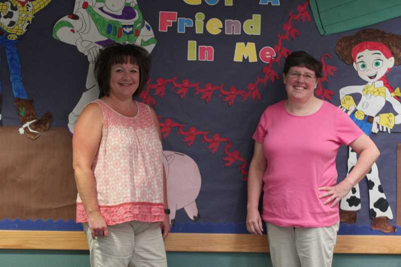 PMG PHOTO: PHIL HAWKINS - Kindergarten teachers Tami Esmay and Cindy Jackson meet with families over the summer at local city parks, providing reading kits to children and helping register new students to the North Marion School District.