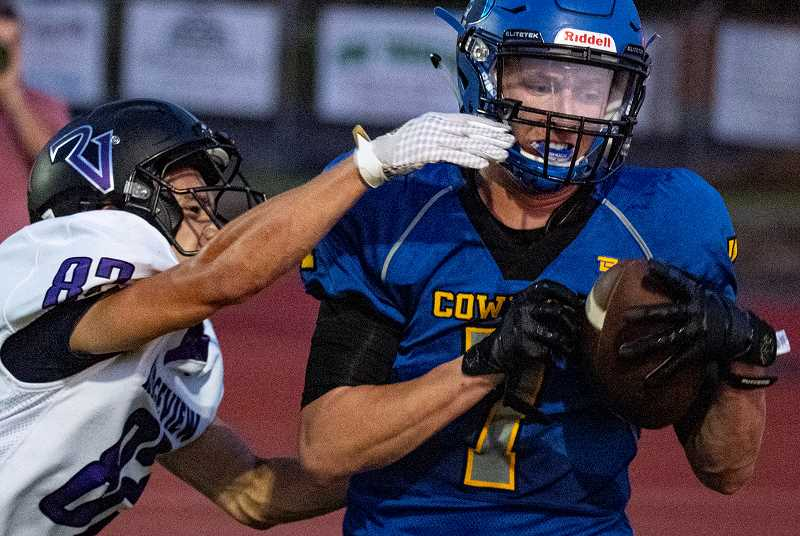 LON AUSTIN/CENTRAL OREGONIAN - Garett Bernard pulls in a touchdown pass against Ridgeview defender Eli Millington during the second quarter of the Cowboys' 39-15 victory over the Ravens. Bernard caught three passes for 44 yards and the touchdown during the game.