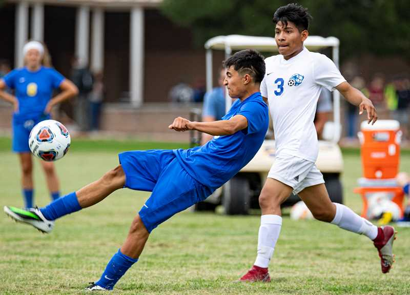 LON AUSTIN/CENTRAL OREGONIAN - Jesse Sanchez plays a ball away from Jesus   Alonso of Madras during the first half of the Cowboys'; match with the White Buffalos. Sanchez scored the first goal of the contest. Crook County led 2-1 midway through the second half of the match before Madras scored five unanswered goals to win 6-2.