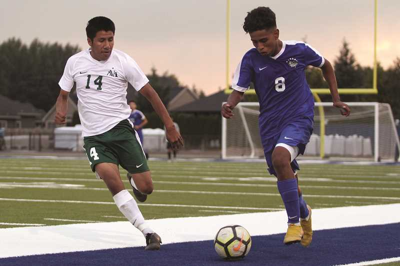 PMG PHOTO: PHIL HAWKINS - Woodburn junior Jimmy Martin (right) looks to advance the ball past North Marion senior Ronaldo Gonzalez in the second half of the Bulldogs' 2-0 win over the Huskies on Thursday.