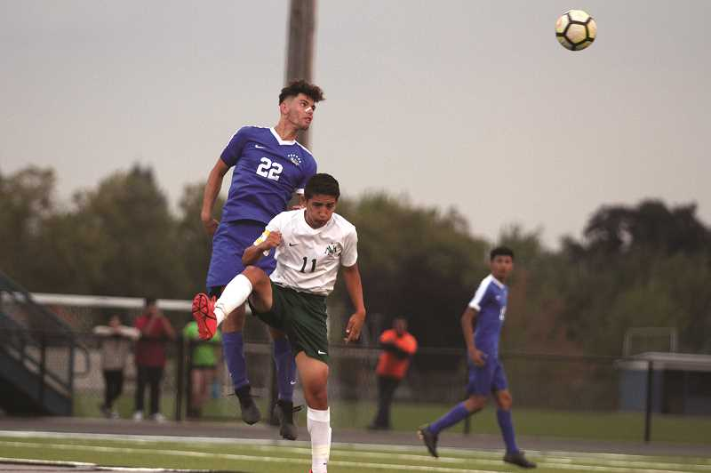 PMG PHOTO: PHIL HAWKINS - Woodburn senior Riley Menezes scored the second goal of the night on a header off a corner kick in the 35th minutes of the game. Fellow senior Kevin Flores opened the contest with the go-ahead goal in the first 10 minutes of play on Thursday.