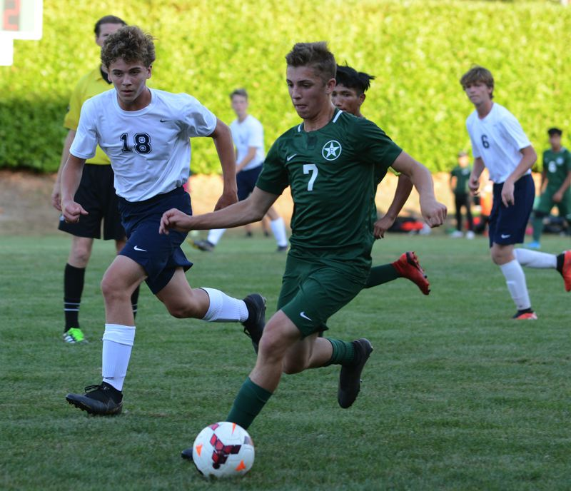 PMG PHOTO: DAVID BALL - Estacada defender Lewis Bever runs onto a loose ball along the sideline during the teams opening win over Banks.