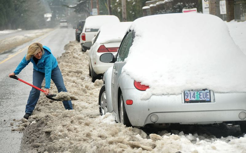 FILE PHOTO - Lauren Huffman works hard to dig out her car parked along Highway 43 in 2013.