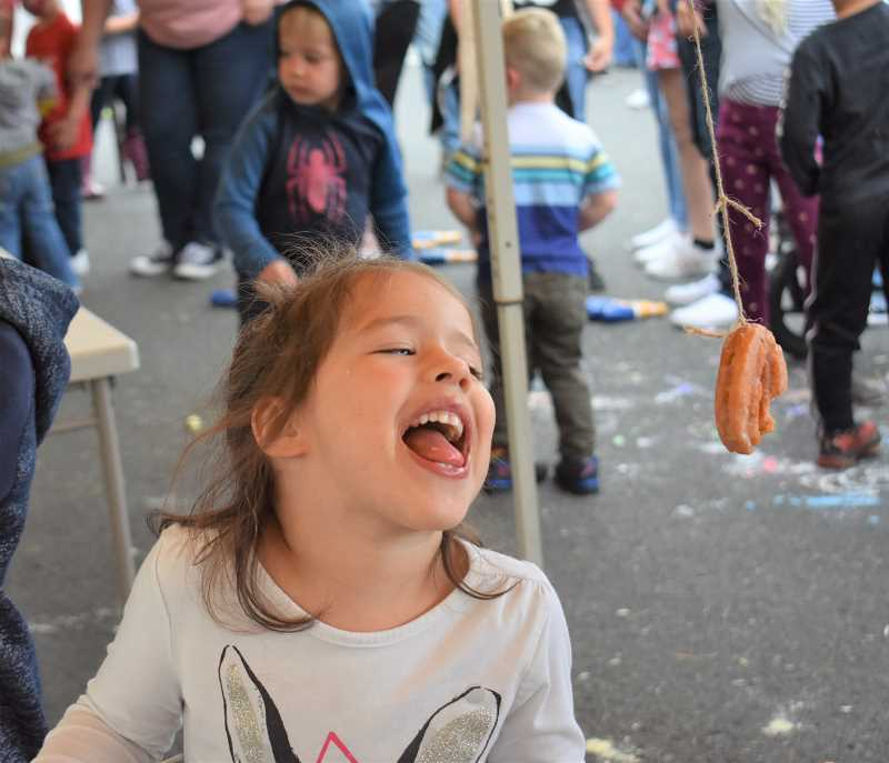 PMG FILE PHOTO - A young attendee of last year's Estacada Harvest Festival strives to catch a doughnut in one of the events games.