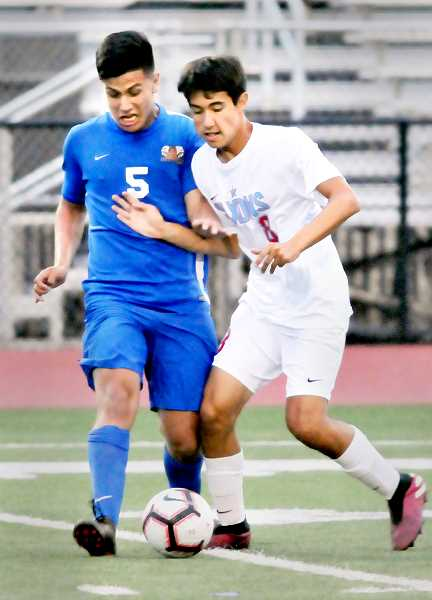 GRAPHIC PHOTO: GARY ALLEN - Freshman midfielder Antonio Guadarrama jockeys with his opponent for the ball in Newberg's 1-0 win over South Salem last Thursday.