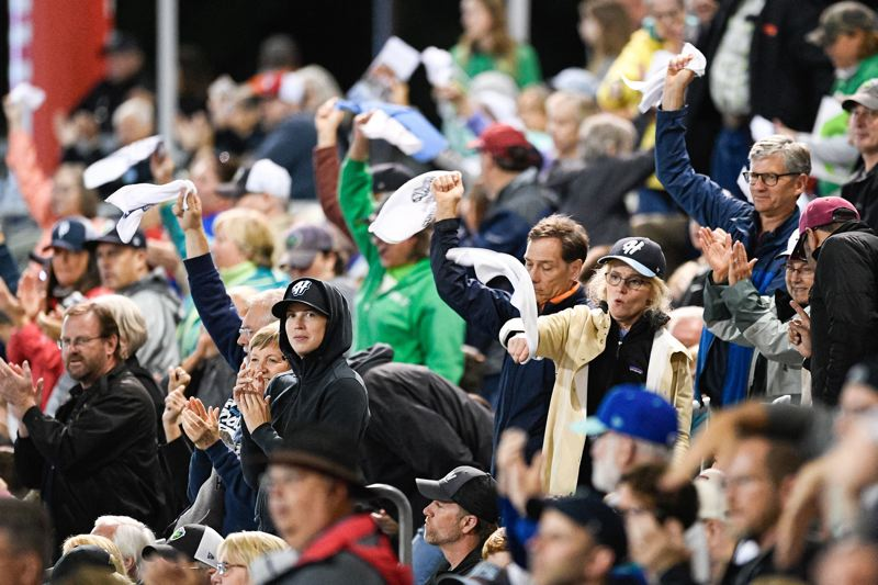 PMG PHOTO: CHRISTOPHER OERTELL - Hillsboro Hops fans wave their towels during the Northwest League Championship Series against the Tri-City Dust Devils at Ron Tonkin Field in Hillsboro last Saturday, Sept. 7.