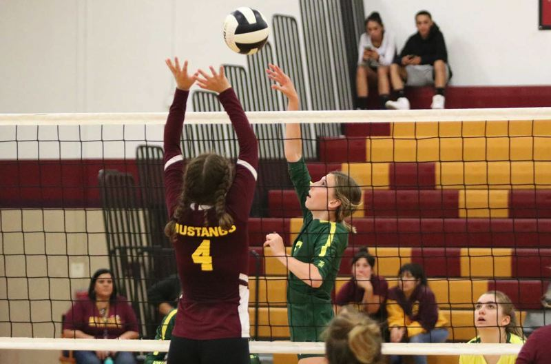 PMG PHOTO: JIM BESEDA - Putnam's Kiana Robertson (green jersey) takes a swing as Milwaukie's Kora Botta (4) goes up for a block during Tuesday's Northwest Oregon Conference volleyball match at Milwaukie High School.