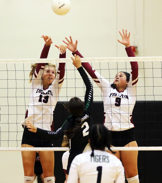 PMG PHOTO: DAN BROOD - Tualatin junior Kylie Zralka (13) and senior Olivia Ashley go up for a block during the first set of the Wolves' match with Tigard.