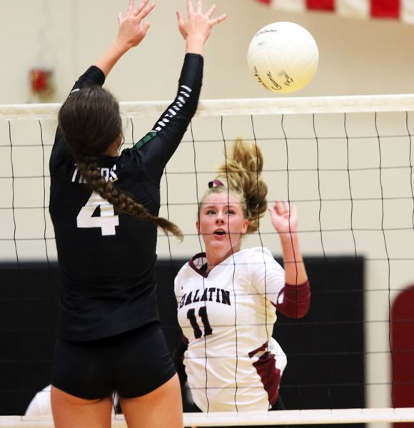 PMG PHOTO: DAN BROOD - Tualatin HIgh School senior Jackie Phillips (11) tries to hit the ball past Tigard junior Avery Croxton during Tuesday's match.