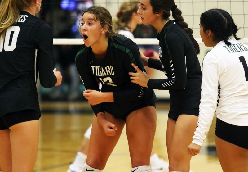 PMG PHOTO: DAN BROOD - Tigard High School sophomore Anna Follett (12) looks to get the Tigers fired up during their league-opening match at Tualatin on Tuesday.