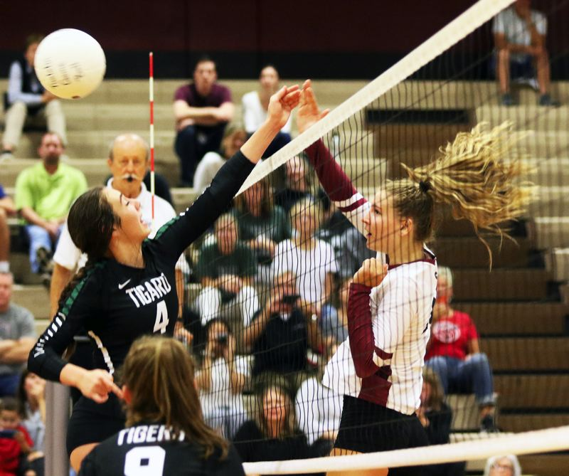 PMG PHOTO: DAN BROOD - Tualatin High School junior Kylie Zralka (right) and Tigard junior Avery Croxton battle at the net during Tuesday's TRL opening match.