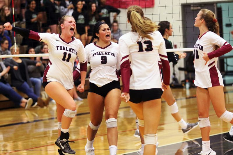 PMG PHOTO: DAN BROOD - Tualatin's (from left) Jackie Phillips, Olivia Ashley, Kylie Zralka and Sophie Biehler celebrate a point during the Wolves' match with Tigard on Tuesday.