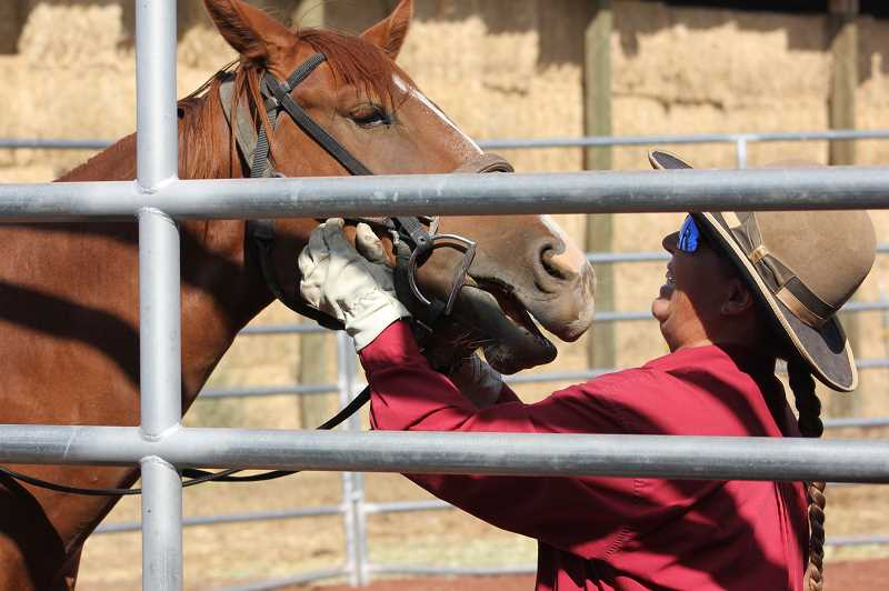 DESIREE BERGSTROM/MADRAS PIONEER  - Kitty Lauman adjusts the bit on the bridal of a horse in a round pen.  Much of what Lauman does with horses relies on communication and showing the animal what they are supposed to be doing.