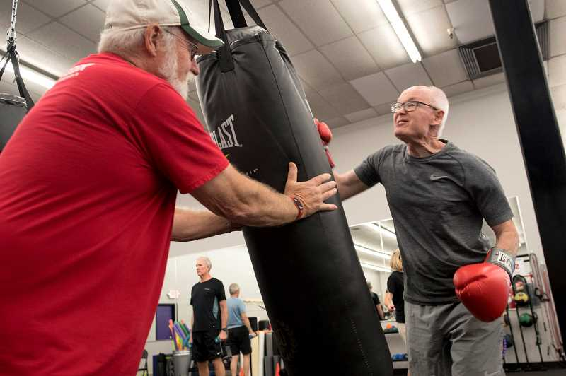 PMG PHOTO: JAIME VALDEZ - Bill Lind, a volunteer with Kimberly Bergs Rebel Fit Club, holds a punching bag for Steve Holland during a session at the studio in downtown Tigard.