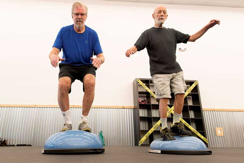 PMG PHOTO: JAIME VALDEZ - Mark Reller (left) and Dennis Bottum work on their core and balance at Kimberly Bergs Rebel Fit Club in downtown Tigard.