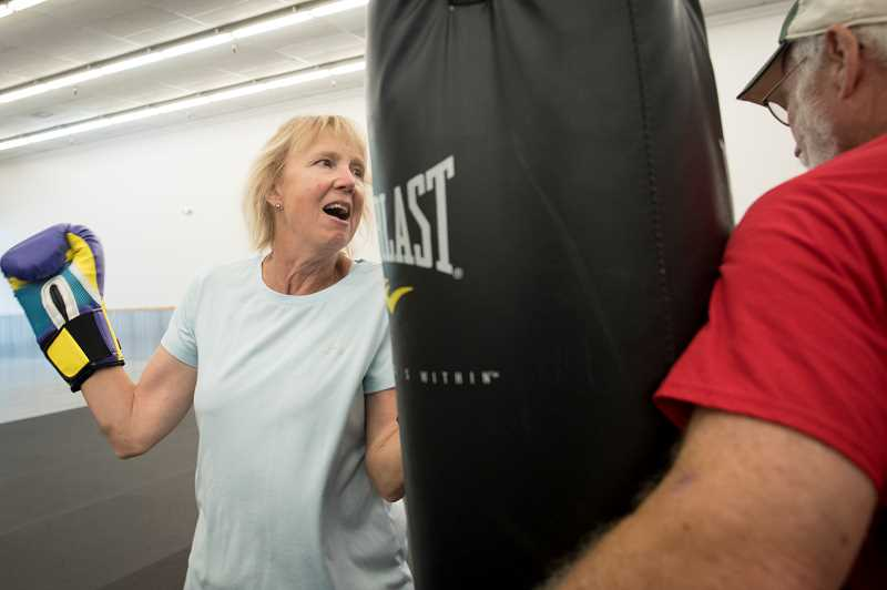 PMG PHOTO: JAIME VALDEZ - Lori Samuals punches the bag as volunteer Bill Lind encourages her at Kimberly Bergs Rebel Fit Club in downtown Tigard.