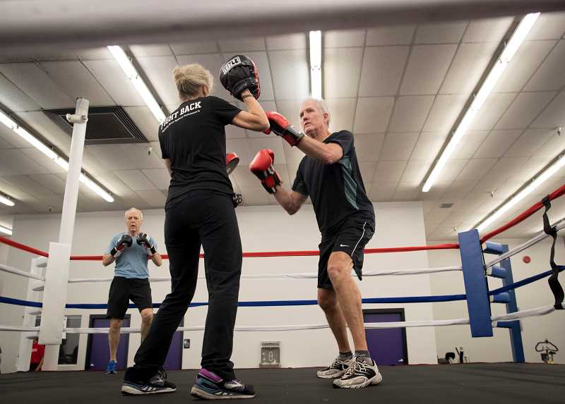 PMG PHOTO: JAIME VALDEZ - Trainer Kimberly Berg works with Gary McGrath as Glenn Hostetter keeps warm by running in the background. Berg who recently opened up her own gym, Kimberly Bergs Rebel Fit Club, in downtown Tigard, works with individuals with Parkinsons disease.