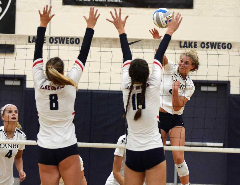 PMG PHOTO: DEREK WILEY - Canby junior Daley McClellan his the ball at a pair of Lake Oswego blockers Tuesday night.