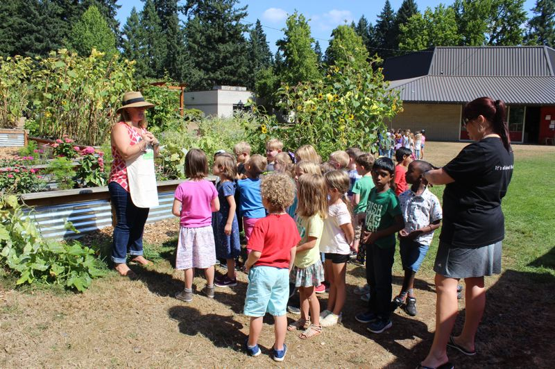 PMG PHOTO: CLAIRE HOLLEY - Parent volunteer Sarah Howell tells Kerri Lees class of new kindergarteners about the River Grove garden.