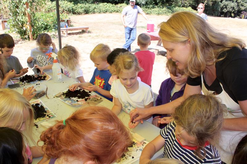 PMG PHOTO: CLAIRE HOLLEY - Laurel Bates helps students find worms in the soil and understand their role in composting.