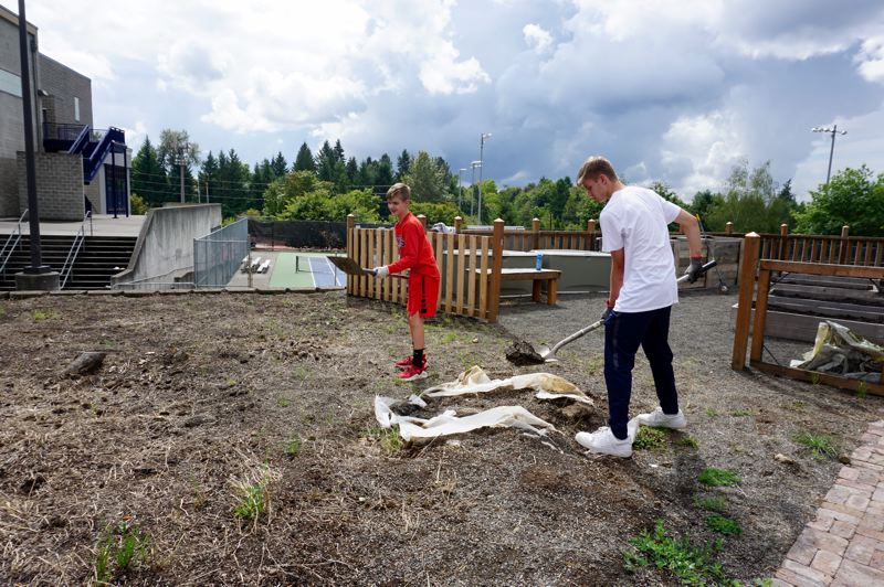 PMG PHOTO: CLAIRE HOLLEY - Justin Metke (left) and Ethan Evans (right) work on the site of the current raised bed garden and future greenhouse.
