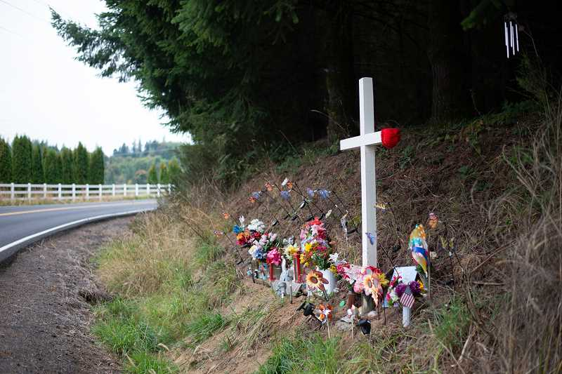 PMG PHOTO: ANNA DEL SAVIO - Six months after her death, a roadside memorial stands near where Sarah Zuber's body was found. A red hat propped on the cross mimics the red hat Zuber was often seen wearing.