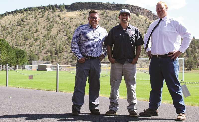 JASON CHANEY - Crook County Judge Seth Crawford (right), Blaine Noland of Blaine Noland Construction and Painting (middle) pose for a photo with Travis Garner, the manager of Parr Lumber, which is providing the paint at a discount. The paint on the 'CC' logo — on the hill just to the left of Garner — has faded in recent years.
