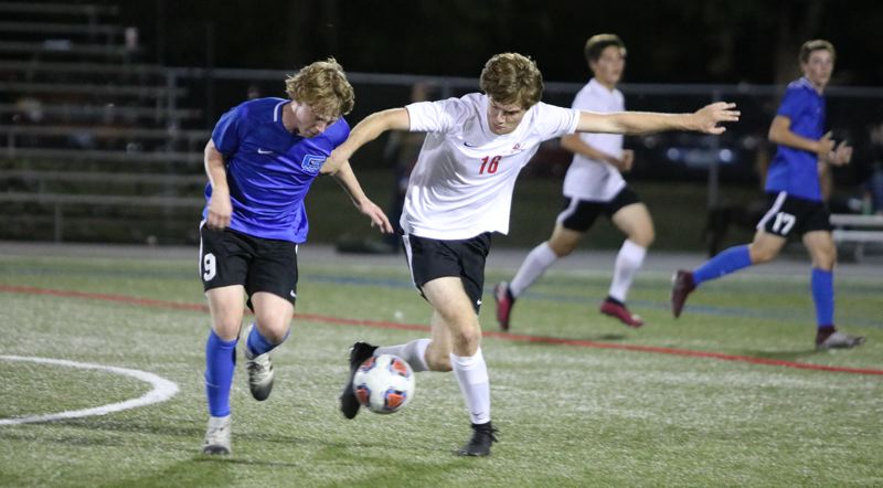 PMG PHOTO: JIM BESEDA - Clackamas' Colm Dady (16) challenges Grant's Nicholas Lattal (9) for possession during the closing minutes of Thursday night's non-conference boys soccer match at Delta Park's Strasser Field.
