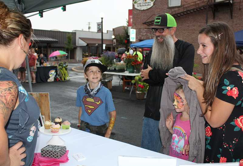 HOLLY M. GILL/MADRAS PIONEER - The Keller family, from right to left, Cassandra, Scarlett, 6, Brian and Eric, 9, check out the cupcakes at the Sara's Sweet Muffins booth, run by Sara Johnston, left.