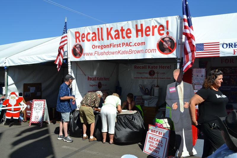 PMG FILE PHOTO - Oregon State Fair visitors sign a petition to recall Gov. Kate Brown at the booth organized by Flush Down Kate Brown.