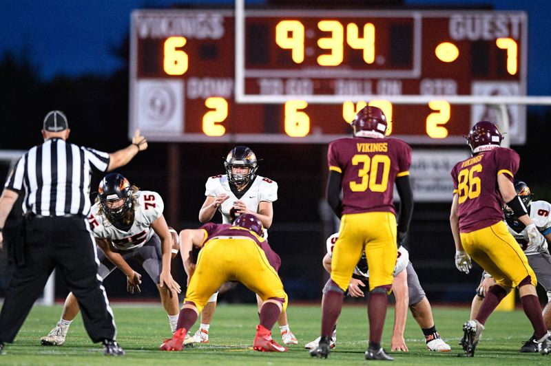 PMG PHOTO: CHRISTOPHER OERTELL - Scappoose High quarterback Jakobi Kessi calls signals during the first half Friday night and Jerico Archer (75) and others prepare to block as the Indians play at Forest Grove.