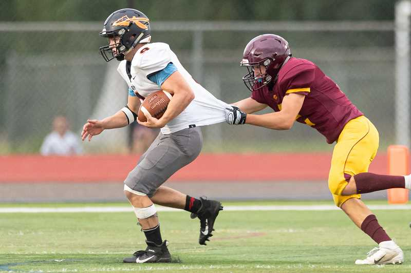 PMG PHOTO: CHRISTOPHER OERTELL - Scappoose's Josh Rice runs away from a Forest Grove defender during the Indians' game with the Vikings Friday night, Sept. 13, at Forest Grove High School.