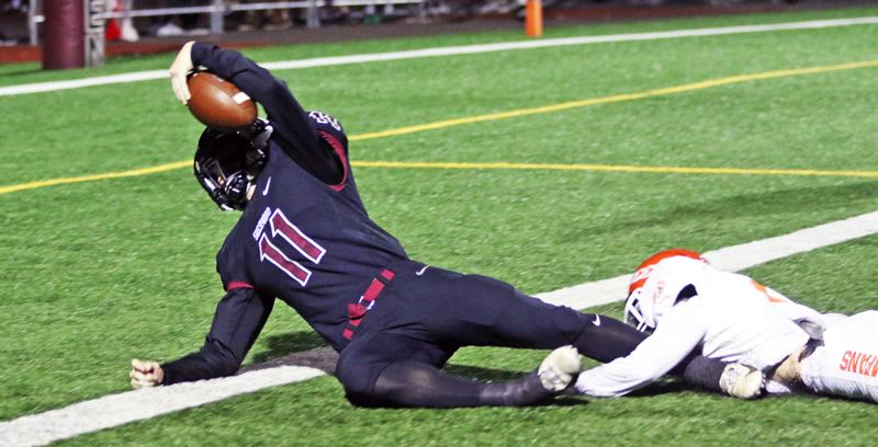 PMG PHOTO: DAN BROOD - Sherwood High School junior Clay Peden (11) reaches the ball over the goal line for his third rushing touchdown of the game in the Bowmen's 42-14 win over Sprague.