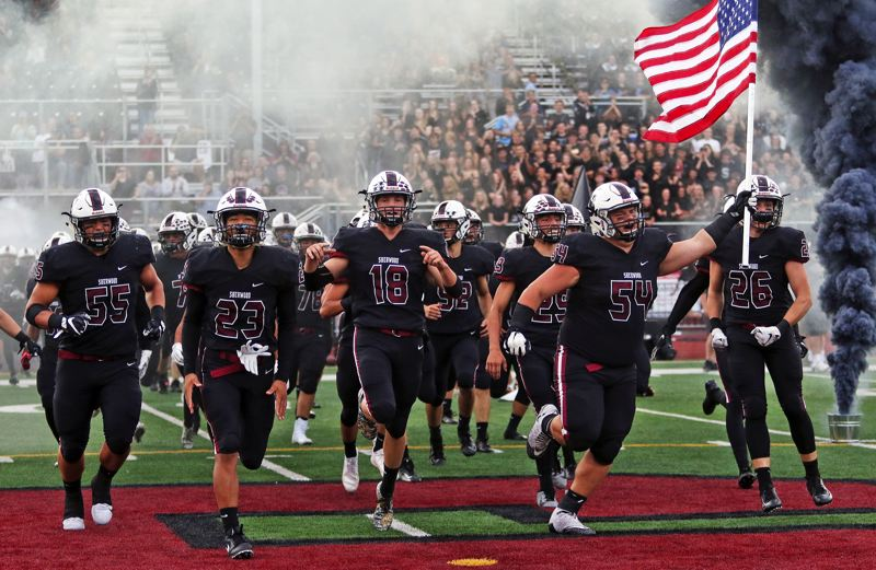 PMG PHOTO: MILES VANCE - The Sherwood football team rolls onto the field carrying the American flag in a cloud of smoke before its 42-14 win over Sprague at Sherwood High School on Friday, Sept. 13.