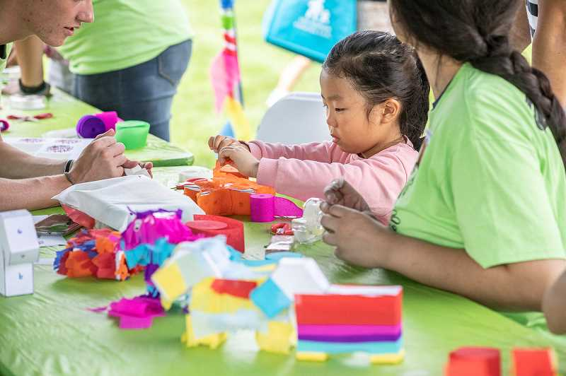 PMG PHOTO: JONATHAN HOUSE - Seorin Lee, 5, of Tualatin, makes a piñata during Viva Tualatin! held Saturday at Tualatin Community Park.