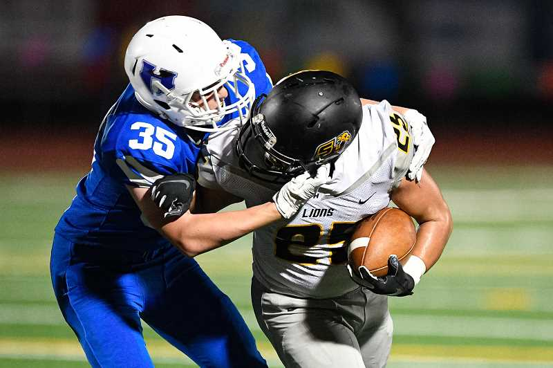 PMG PHOTO: CHRISTOPHER OERTELL - Hillsboro's Ryan Benedict (35) tackles St. Helens' Jacobi Allen (25) during the Spartans' football game versus the Lions at Hare Field in Hillsboro, Ore., on Friday, Sept. 13, 2019.