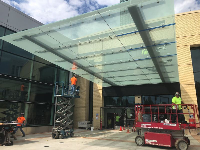 PMG PHOTO: STEPHANIE BASALYGA - Crews working on a renovation project at the Oregon Convention Center install a new canopy over an entrance along Martin Luther King Jr. Boulevard.